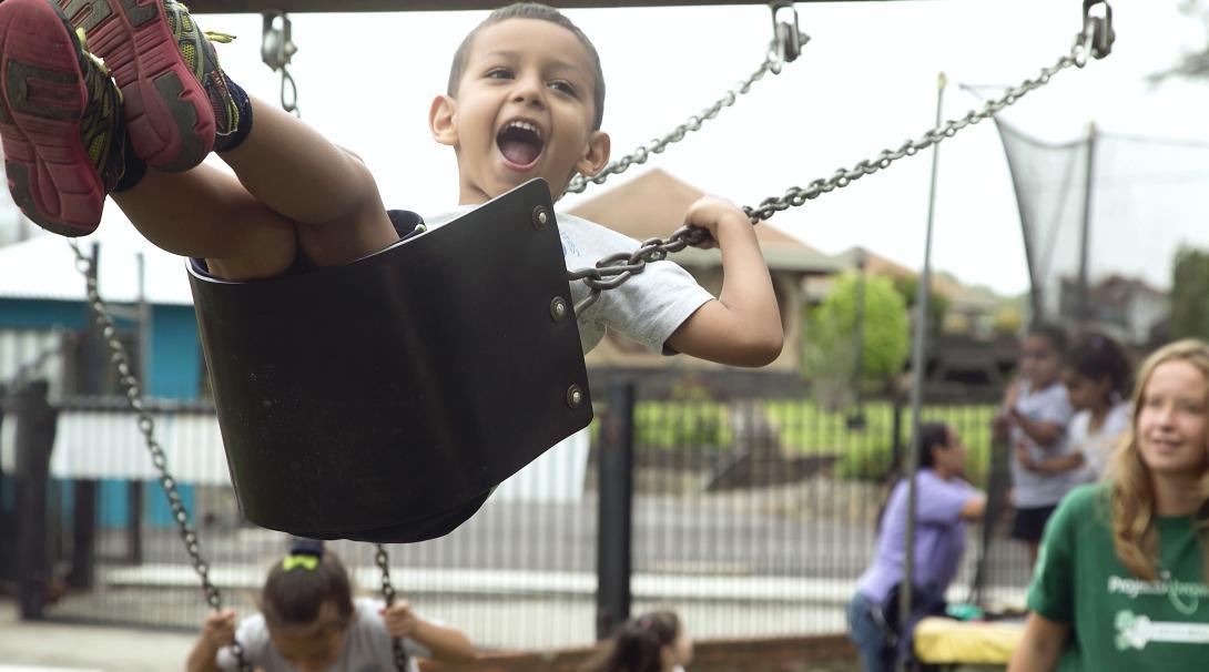 Des volontaires dans le développement de la petite enfance poussent un écolier sur un balançoire au cours de leur projet au Costa Rica.